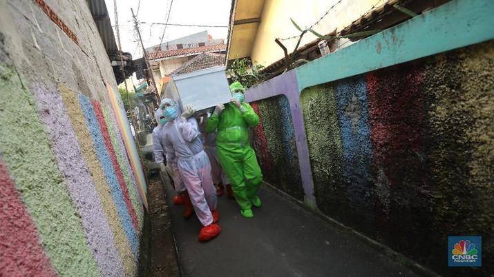 Sejumlah satgas pemulasaran jenazah covid-19 bersiap untuk memakamkan jenazah covid-19 yang meninggal saat isolasi mandiri di Jalan Camat Gabung, Jagakarsa, Lenteng agung, Jakarta, Jumat (16/7/2021). (CNBC Indonesia/Andrean Kristianto)