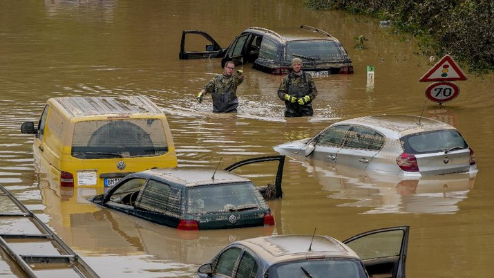 Helpers check for victims in flooded cars on a road in Erftstadt, Germany, Saturday, July 17, 2021. Due to strong rainfall,  the small Erft river went over its banks,  causing massive damage. (AP Photo/Michael Probst)