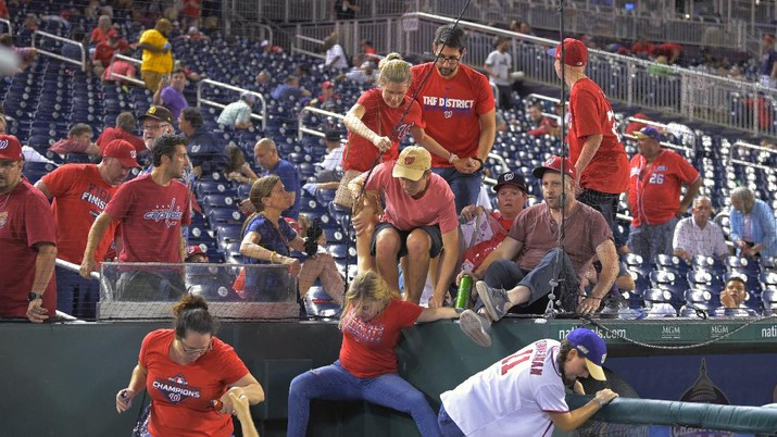 Fans jump into a camera well after hearing gunfire from outside the stadium, during a baseball game between the San Diego Padres and the Washington Nationals at Nationals Park in Washington on Saturday, July 17, 2021. (John McDonnell/The Washington Post via AP)