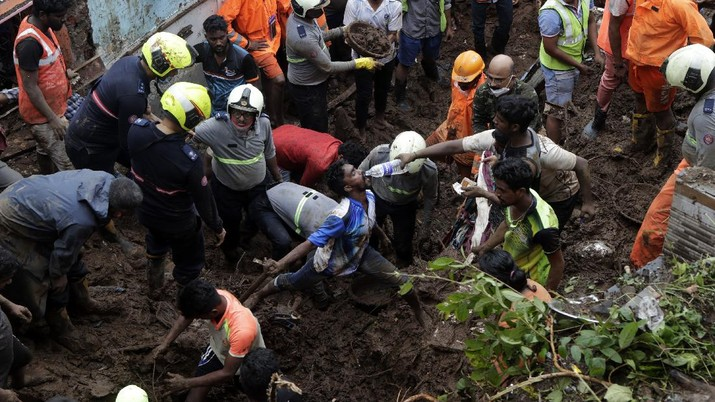 Rescuers carry a dead body of a man after a wall collapsed on several slum houses heavy monsoon rains in the Mahul area of Mumbai, India, Sunday, July 18, 2021. More than a dozen people were killed in the incident. (AP Photo/Rajanish Kakade)