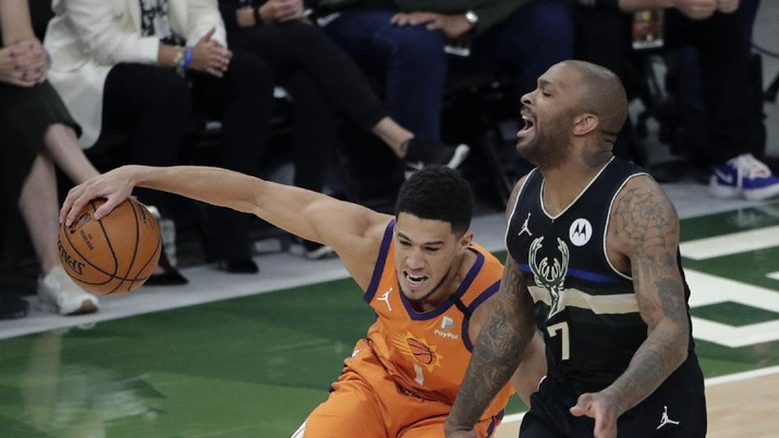 Phoenix Suns guard Devin Booker (1) works the ball against Milwaukee Bucks guard Bryn Forbes (7) during the first half of Game 6 of basketball's NBA Finals Tuesday, July 20, 2021, in Milwaukee. (AP Photo/Aaron Gash)