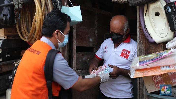 Petugas PT Pos Indonesia melakukan penyaluran Bantuan Sosial Tunai secara door to door di Kawasan Petojo Selatan, Jakarta, Rabu (21/7/2021). Tahun ini bansos (BST) ditargetkan untuk menjangkau hingga 10 juta keluarga penerima, penyaluran pun dilakukan secara bertahap.   (CNBC Indonesia/ Tri Susilo)