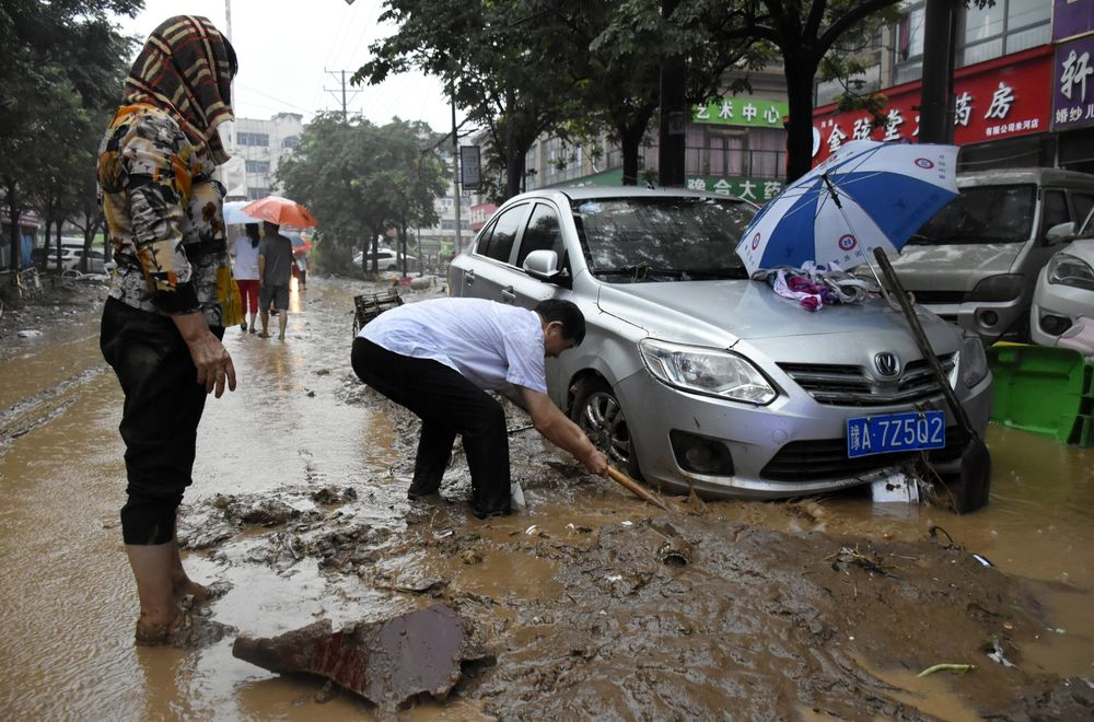 In this photo released by Xinhua News Agency, residents clean up the aftermath of a flood in Mihe Town of Gongyi City, in central China's Henan province on Wednesday, July 21, 2021. China's military has blasted a dam to release floodwaters threatening one of its most heavily populated provinces, as the death toll in widespread flooding rose to more than two dozens. (Han Chaoyang/Xinhua via AP)