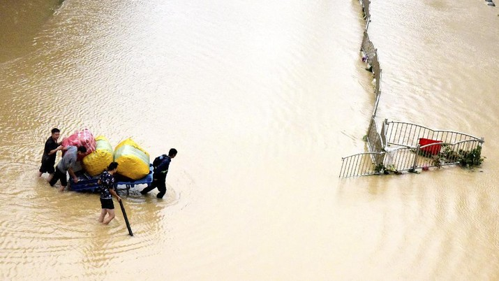 In this photo released by Xinhua News Agency, residents move their belongings across a flooded street in Zhengzhou in central China's Henan province on Wednesday, July 21, 2021. China's military has blasted a dam to release floodwaters threatening one of its most heavily populated provinces, as the death toll in widespread flooding rose to more than two dozens. (Zhu Xiang/Xinhua via AP)