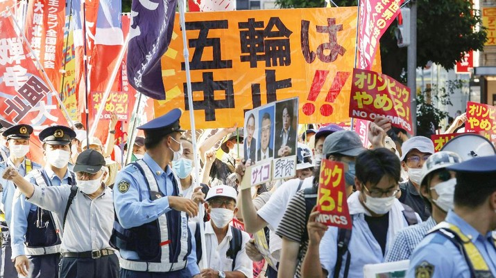 Anti-Olympics protesters march with banners in Tokyo on the opening day of the Tokyo 2020 Olympics Friday, July 23, 2021. A sign, center, reads