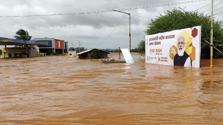 A billboard with a photograph of Prime Minister Narendra Modi is partially submerged in flood waters at Kolhapur in western Maharashtra state, India, Saturday, July 24, 2021. Officials say landslides and flooding triggered by heavy monsoon rain have killed more than 100 people in western India. More than 1,000 people trapped by floodwaters have been rescued. (AP Photo)