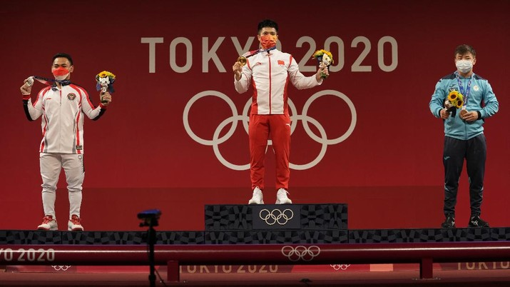Gold medalist Li Fabin of China, center, stands with silver medalist Eco Yuli Irawan of Indonesia, left, and bronze medalist Igor Son of Kazakhstan, right, after the men's women's kg weightlifting competition in the men's 61kg weightlifting event, at the 2020 Summer Olympics, Sunday, July 25, 2021, in Tokyo, Japan. (AP Photo/Luca Bruno)