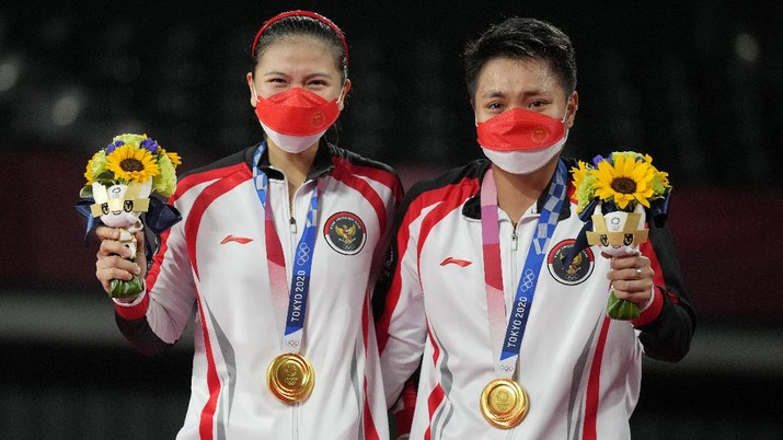 Indonesia's Greysia Polii, right, and Apriyani Rahayu celebrate with their gold medals after defeating China's Chen Qing Chen and Jia Yi Fan during their women's doubles gold medal match at the 2020 Summer Olympics, Monday, Aug. 2, 2021, in Tokyo, Japan. (AP Photo/Dita Alangkara)