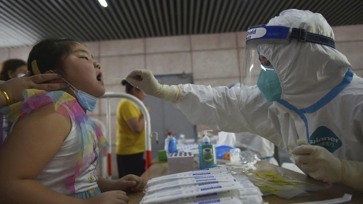 A nurse takes throat swab samples in new round of COVID-19 testing in Nanjing city in eastern China's Jiangsu province Monday, Aug. 2, 2021. The current coronavirus outbreaks in China, while still in the hundreds of cases in total, have spread much more widely than previous ones, reaching multiple provinces and cities including the capital, Beijing. Many of the cases have been identified as the highly contagious delta variant that is driving a resurgence in many countries. (Chinatopix via AP)