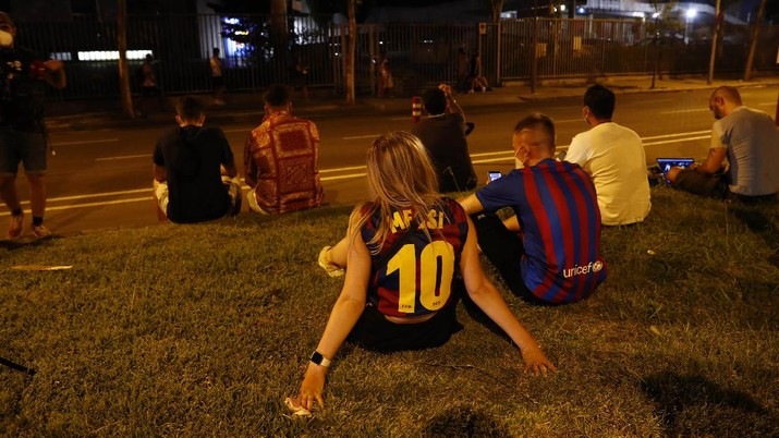 A fan wearing the number 10 Lionel Messi replica shirt sits outside the club offices with others in Barcelona, Spain, Thursday, Aug. 5, 2021. Barcelona announced Thursday that Messi will not stay with the club, saying that the Spanish league's financial regulations made it impossible to sign the Argentina star to a new contract. (AP Photo/Joan Monfort)