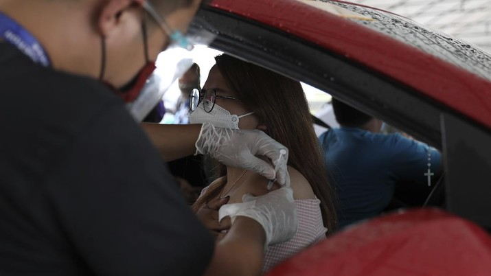 A woman reacts as she receives a shot of the Pfizer COVID-19 vaccine at a drive-thru vaccination site during a stricter lockdown in Manila, Philippines on Friday. August 6, 2021. Thousands of people jammed coronavirus vaccination centers in the Philippine capital, defying social distancing restrictions, after false news spread that unvaccinated residents would be deprived of cash aid or barred from leaving home during a two-week lockdown that started Friday. (AP Photo/Basilio Sepe)