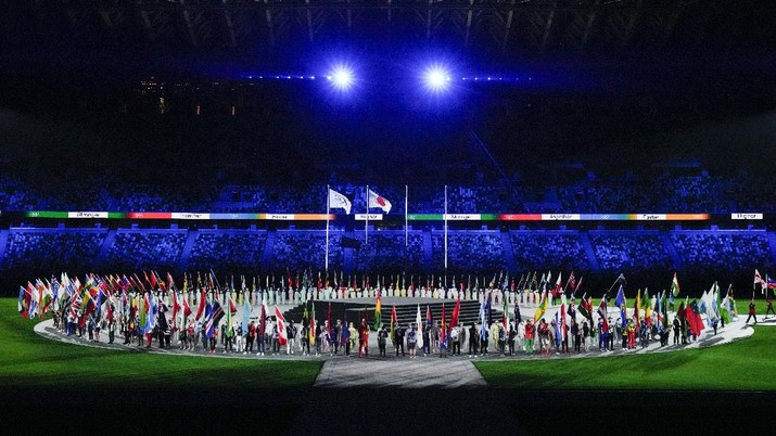 Flags are carried in during the closing ceremony in the Olympic Stadium at the 2020 Summer Olympics, Sunday, Aug. 8, 2021, in Tokyo, Japan. (AP Photo/Charlie Riedel)