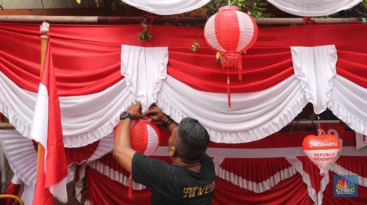 Pedagang memasang pernak pernik bendera di kawasan Pasar Kramat Jati, Jakarta, Senin (9/8/2021). Pedagang mengeluhkan sepinya pembeli, momentum Hari Kemerdekaan RI seharusnya menjadi ladang rezeki dari menjual pernak pernik hiasan bendera merah putih.  Sahir (25) menjual pernak-pernik bendera sejak tahun 2013 ini mengatakan