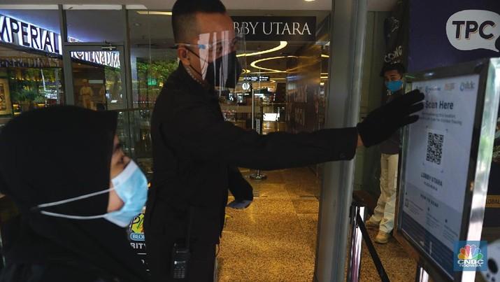 Petugas memberikan informasi scan code vaksin kepada pengunjung yang akan masuk ke dalam Mal Blok M Plaza, Jakarta, Selasa (10/8/2021). Pemerintah mengumumkan kembali memperpanjang PPKM hingga 16 Agustus 2021. Dalam perpanjangan kali ini pusat perbelanjaan atau mal di wilayah PPKM level 4 bisa dibuka dalam kapasitas 25%.  (CNBC Indonesia/ Tri Susilo)