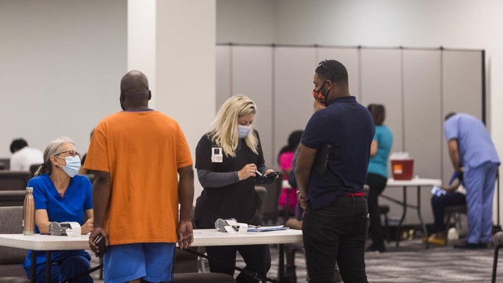 In this photo provided by Impact Church, people register for a COVID-19 vaccination at an event held by Impact Church on Aug. 8, 2021, in Jacksonville, Fla. The church has lost seven members in the last few weeks, Pastor George Davis said Wednesday, Aug. 11. (Impact Church via AP)