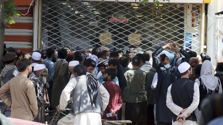 Afghans wait for hours to try to withdraw money, in front of Kabul Bank, in Kabul, Afghanistan, Saturday, Aug. 28, 2021. (AP Photo/Khwaja Tawfiq Sediqi)
