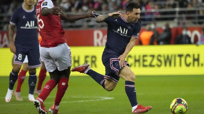 Reims' Marshall Munetsi, left, challenges for the ball with PSG's Lionel Messi during the France League One soccer match between Reims and Paris Saint-Germain, at the Stade Auguste-Delaune in Reims, France, Sunday, Aug. 29, 2021. (AP Photo/Francois Mori)