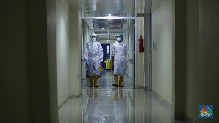 Petugas kesehatan memeriksa pasien Covid-19 diruangan Instalasi Gawat Darurat (IGD) di RSUD Koja, Jakarta, Senin (30/8/2021). Jumlah pasien Covid-19 yang dirawat di RSUD Koja terus menurun dengan peningkatan pasien sembuh.   Diruangan IGD hanya ada tiga pasien Covid-19 yang sedang ditangani lebih lanjut.   Di ruangan bayi terisi dua bayi berada didalam inkubator dengan penanganan khusus dari para nakes. Berdasarkan data Kementerian Kesehatan (Kemenkes) kasus konfirmasi positif Covid-19 di tanah air hari ini bertambah 5.436 kasus, menurun dibandingkan dengan sehari sebelumnya 7.427 kasus.  Dengan pertambahan ini maka total kasus konfirmasi positif Covid-19 di Indonesia mencapai 4,079 juta. Sementara, jumlah pasien sembuh bertambah 19.398 orang pada hari ini, sehingga total kasus sembuh menjadi 3.743.716. (CNBC Indonesia/ Tri Susilo)