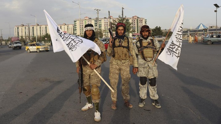 Taliban fighters hold Taliban flags in Kabul, Afghanistan, Monday, Aug. 30, 2021. Many Afghans are anxious about the Taliban rule and are figuring out ways to get out of Afghanistan. But it's the financial desperation that seems to hang heavy over the city. (AP Photo/Khwaja Tawfiq Sediqi)