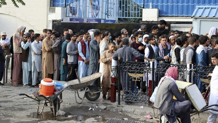 Afghans wait in long lines for hours to try to withdraw money, in front of a bank in Kabul, Afghanistan, Monday, Aug. 30, 2021. The Taliban have limited weekly withdrawals to $200. (AP Photo/Khwaja Tawfiq Sediqi)