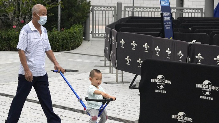 An elderly man pushes a child near barricades outside the Universal Studios theme park during trial runs in Beijing, China, Tuesday, Aug. 31, 2021. Universal Studios announced Monday, Aug. 30, 2021, that its first theme park in China will open in the country's capital in September. The company set the opening date for Sept. 20, according to a statement and video posted on the Chinese social media site WeChat. (AP Photo/Ng Han Guan)