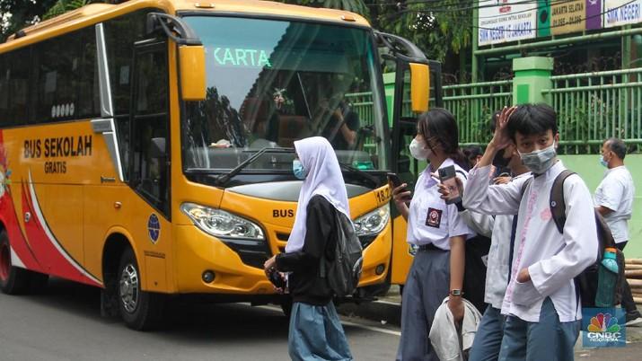 Sejumlah pelajar menaiki bus sekolah usai mengikuti pembelajaran tatap muka (PTM) di SMK Negeri 15, Kebayoran Baru, Jakarta Selatan, Jumat (3/9). Dinas Perhubungan DKI Jakarta melalui Unit Pengelola (UP) Angkutan Sekolah membantu sarana transportasi gratis bagi peserta didik yang mengikuti PTM secara terbatas dengan mengoperasikan 70 bus sekolah yang melayani 20 rute reguler dan 13 rute zonasi. Sebelum digunakan bus sekolah yang layani antar dan jemput pelajar juga terlebih dahulu disemprot cairan disinfektan. Pelajar yang akan menggunakan layanan antar dan jemput bus sekolah juga wajib menerapkan protokol kesehatan dengan menggunakan masker dan menjaga jarak saat berada di dalam bus. (CNBC Indonesia/ Muhammad Sabki)