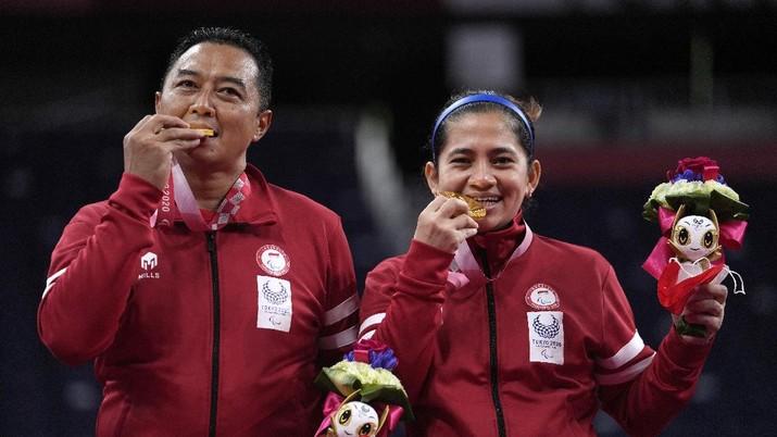 Hary Susanto dari Indonesia, kiri, dan Leani Ratri Oktila berfoto setelah menerima medali emas untuk pertandingan perebutan medali emas ganda campuran SL3-SU5 di Paralympic Games Tokyo 2020, Minggu, (5/9/2021) di Tokyo, Jepang. (AP/Kiichiro Sato)
