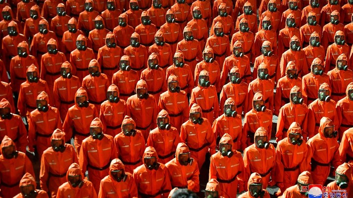 Parade militer besar-besaran Korut yang terbaru menampilkan barisan personel yang memakai baju hazmat warna oranye. (via REUTERS/KCNA)