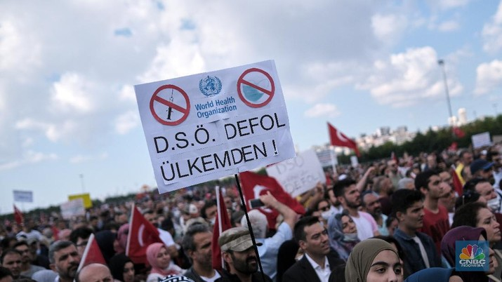 A demonstrator holds a placard reading