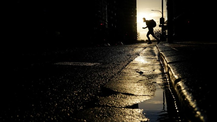 A pedestrian crosses a street at sunset in the city centre during a lockdown to curb the spread of a coronavirus disease (COVID-19) outbreak in Sydney, Australia, September 14, 2021.  REUTERS/Loren Elliott     TPX IMAGES OF THE DAY