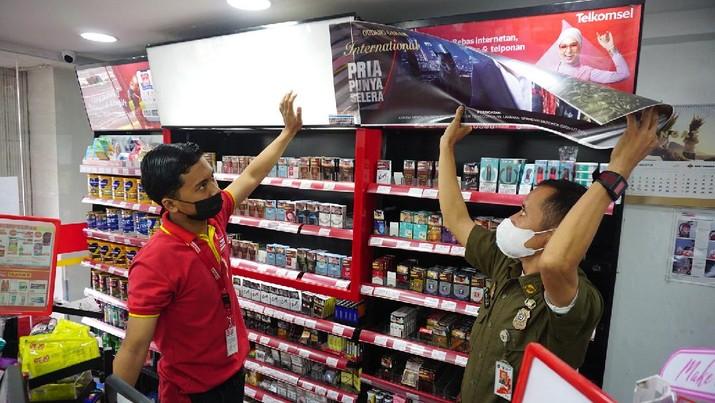 Petugas Satpol PP Jakarta Barat menutup gerai minimarket yang menjual rokok di Alfamart, Jakarta Barat, Selasa (14/9/2021). (CNBC Indonesia/Tri Susilo)