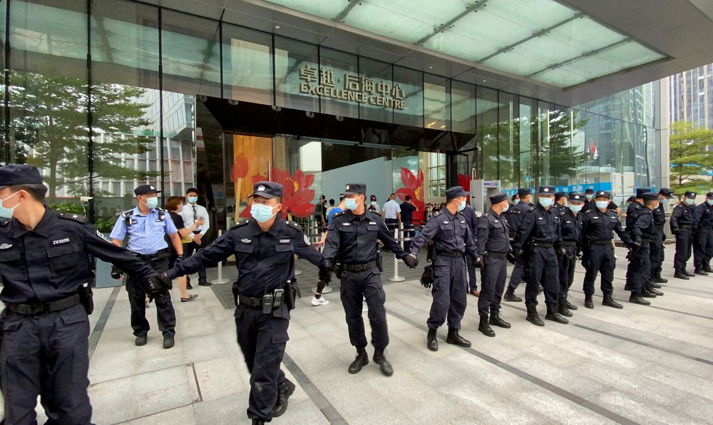 FILE PHOTO: People gather to demand repayment of loans and financial products at the lobby of Evergrande's Shenzhen headquarter, Guangdong province, China September 13, 2021. REUTERS/David Kirton/File Photo
