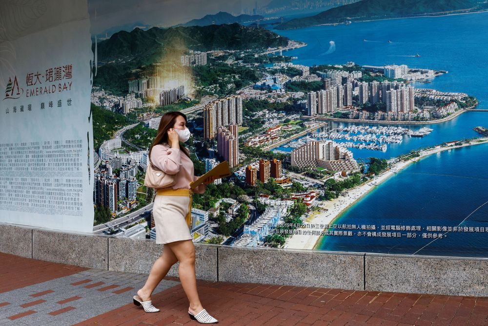 A woman walks past a property advertisement for Emerald Bay by China Evergrande in Hong Kong, China. August 25, 2021. REUTERS/Tyrone Siu