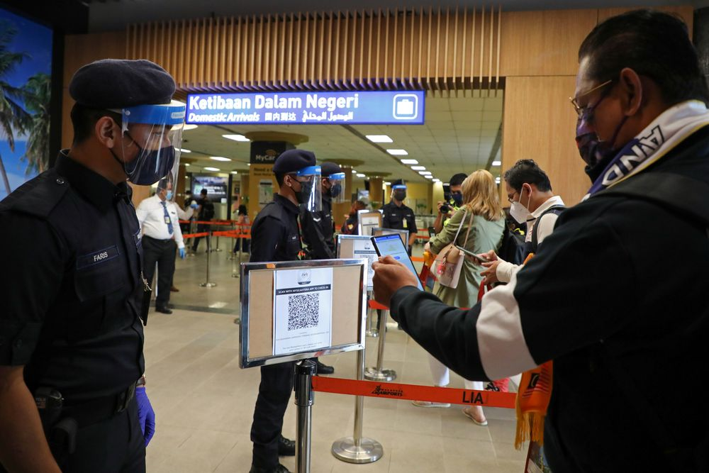 A tourist scans a QR code to check in upon arriving at the airport as Langkawi reopens to domestic tourists, amid the coronavirus disease (COVID-19) pandemic in Malaysia September 16, 2021. REUTERS/Lim Huey Teng
