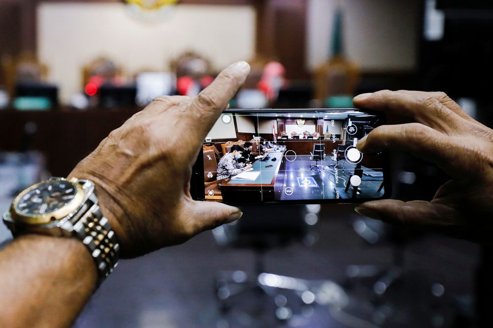 A man takes pictures on a smartphone during the hearing of a citizen lawsuit, done in an attempt to sue the government into taking action on the city's chronic levels of air pollution, at the Central Jakarta Court, Indonesia, September 16, 2021. REUTERS/Willy Kurniawan   REFILE - QUALITY REPEAT