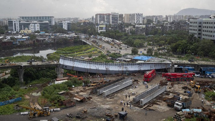 Workers stand near an under-construction bridge that collapsed in Mumbai, India, Friday, Sept. 17, 2021. According to police more than a dozen people were injured after a part of the under-construction bridge collapsed early Friday morning in Mumbai. (AP Photo/Rafiq Maqbool)