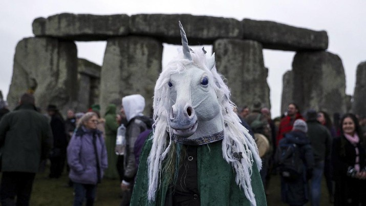 A person wears a costume as people gather at Stonehenge in Wiltshire, western England, on the winter solstice to witness the sunrise after the longest night of the year Friday Dec. 22, 2017. (Andrew Matthews/PA via AP)