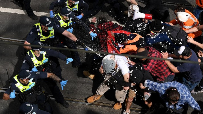 A protester is detained by Victoria police during a