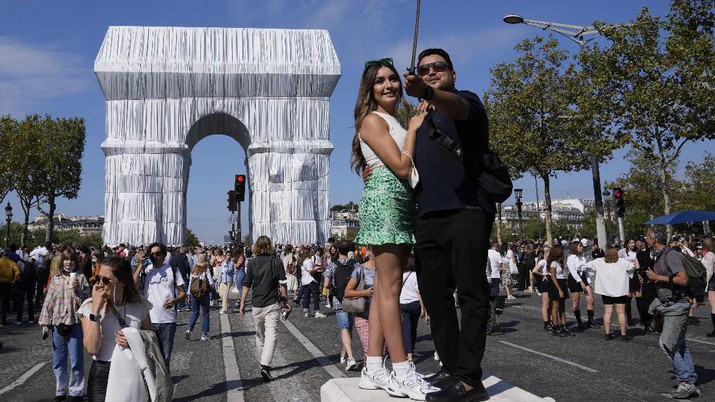 Mexican tourists pose for a selfie in front of the wrapped Arc de Triomphe monument Saturday, Sept. 18, 2021 in Paris. The