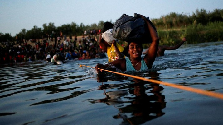 Migrants seeking refuge in the United States walk back into the Mexican side carrying their belongings inside plastic bags while crossing the Rio Bravo river which divides the border between Ciudad Acuna, Mexico and Del Rio, Texas, U.S., to avoid being deported, in Ciudad Acuna, Mexico, September 19, 2021. REUTERS/Daniel Becerril   REFILE- QUALITY REPEAT