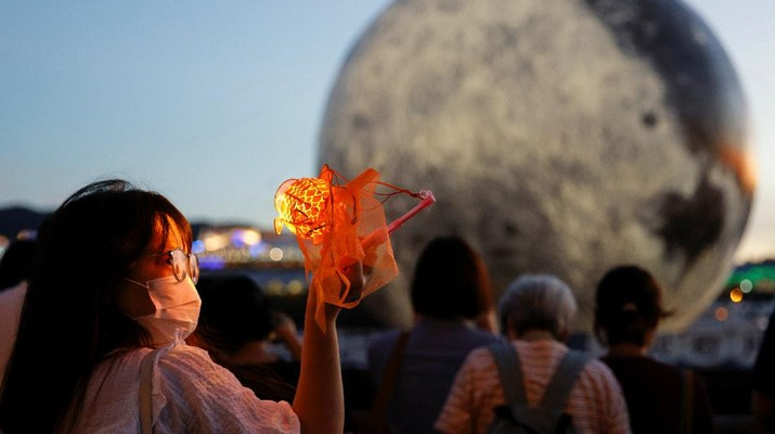 A woman poses for a photo in front of a giant moon-shaped balloon ahead of Mid-Autumn Festival, in Hong Kong, China September 20, 2021. REUTERS/Tyrone Siu