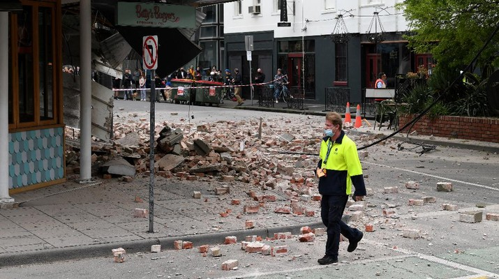 A person walks past damage to the exterior of a restaurant following an earthquake in the Windsor suburb of Melbourne, Australia, September 22, 2021.  AAP Image/James Ross via REUTERS  ATTENTION EDITORS - THIS IMAGE WAS PROVIDED BY A THIRD PARTY. NO RESALES. NO ARCHIVES. AUSTRALIA OUT. NEW ZEALAND OUT