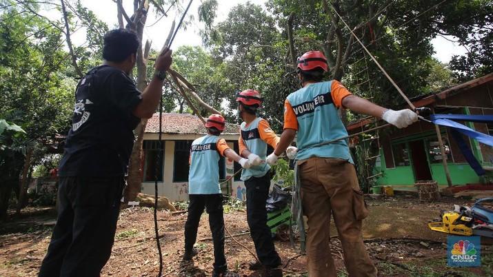 Sejumlah relawan dibantu para guru sekolah alam saat melakukan evakuasi pohon tumbang akibat puting beliung di Depok, Jawa Barat, Rabu 22 September 2021. Kawasan Depok dilanda hujan angin hingga hujan es di daerah Beji, Kota Depok kemarin (21/9) sore. Akibat hujan angin di Depok, pohon tumbang pun tak bisa dielakkan. Berdasarkan data Pemadam Kebakaran (Damkar), setidaknya ada enam lokasi pohon tumbang di Depok. Sejumlah relawan hingga kini mengevakuasi potongan pohon yg menimpa bagian yang rusak  kanopi. Akibat kejadian tersebut proses kegiatan belajar mengajar untuk sementara diberhentikan. Salah satu guru di sekolah alam, Ode mengatakan tidak ada korban jiwa. Kerugian hanya materil dan  pohon yang menimpa atap sekolah. (CNBC Indonesia/ Muhammad Sabki)