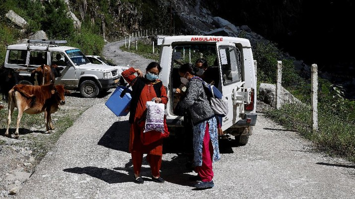 Health workers carry medical kits and a box containing COVISHIELD vaccines, before starting their trek through the mountains to vaccinate people in remote villages, as a part of a vaccination drive, during the coronavirus disease (COVID-19) outbreak, near Malana village in Kullu district in the Himalayan state of Himachal Pradesh, India, September 14, 2021. Despite the hostile terrain, the northern state of Himachal Pradesh became the first in India to administer at least one COVID-19 vaccine dose in all its adults. The steep topography was a challenge overcome by health workers walking for hours or days to reach remote villages.  REUTERS/Adnan Abidi      SEARCH