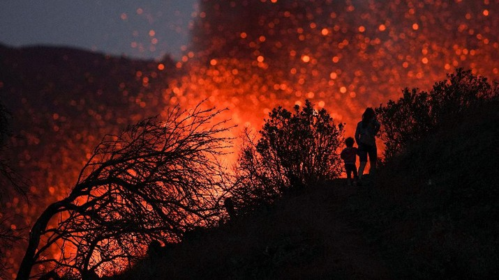 A woman climbs a hill with a child to see the Cumbre Vieja volcano as it continues to erupt in Tacande de Arriba on the Canary Island of La Palma, Spain, October 2, 2021. REUTERS/Juan Medina     TPX IMAGES OF THE DAY