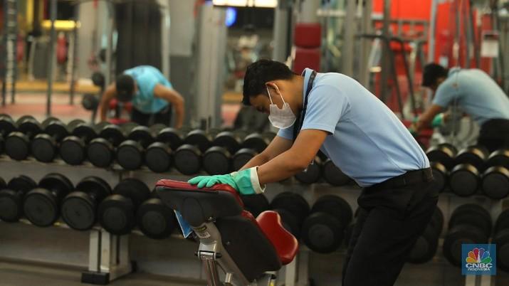Petugas fasilitas kebugaran Fitness First melakukan pembersihan alat kebugaran di salah satu mal di Jakarta, Selasa (5/10/2021).  (CNBC Indonesia/Tri Susilo)