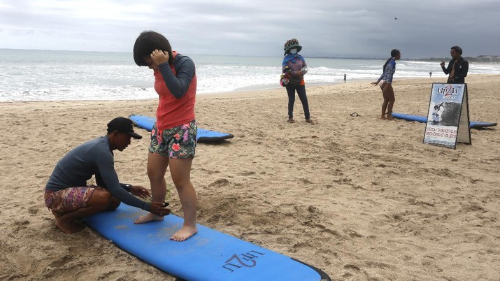 A surf instructor prepares for surf lesson to a tourist at Kuta beach, Bali, Indonesia on Wednesday, Oct. 6, 2021. Indonesia plans to reopen the airport in the resort island of Bali for international flights on Oct. 14, after closing it for more than a year because of the COVID-19 pandemic. (AP Photo/Firdia Lisnawati)