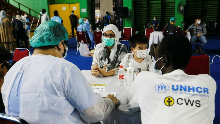 A woman undergoes a health screening before receiving a dose of a vaccine against the coronavirus disease (COVID-19) during a mass vaccination program for asylum seekers and refugees at a sports hall in Jakarta, Indonesia, October 7, 2021. REUTERS/Ajeng Dinar Ulfiana
