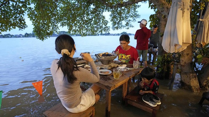Banjir bikin Restoran di Thailand ramai pengunjung. (AP/Sakchai Lalit)