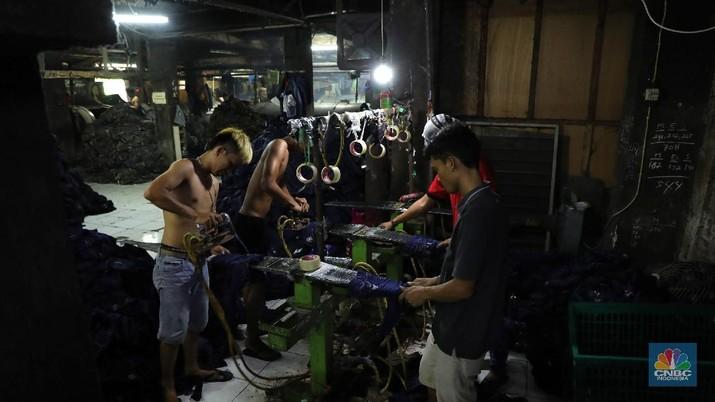 Pekerja menyelesaikan proses pewarnaan dan pencucian pakaian di salah satu pabrik dikawasan Jakarta, Selasa (11/10/2021). Industri tekstil dan produksi tekstil (TPT) mengalami pasang surut sejak pandemi Covid-19 sejak beberapa tahun belakangan. Setelah sebelumnya berhasil bangkit kembali pada kuartal IV 2020, Pemberlakuan Pembatasan Kegiatan Masyarakat (PPKM) mikro pada tahun ini kembali bergeliat. Kontribusi penurunan terbesar berasal dari penurunan pakaian jadi yang memiliki porsi 66% dari total ekspor TPT Indonesia. Tekanan terhadap industri TPT setidaknya masih terjadi hingga paruh pertama 2021. Kinerja TPT sedikit terbantu oleh adanya permintaan Alat Pelindung Diri atau APD untuk keperluan penanganan COVID-19. Namun permintaan terhadap APD tersebut tidak cukup besar untuk menutupi turunnya penjualan produk produk TPT secara keseluruhan. Menurut owner Helmi
